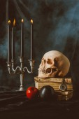 candelabrum, halloween skull, ancient books with black and red apples on black cloth with smoke