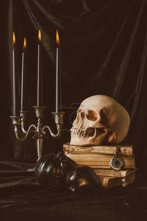 halloween skull on ancient books with black pumpkin, apple and candles on black cloth