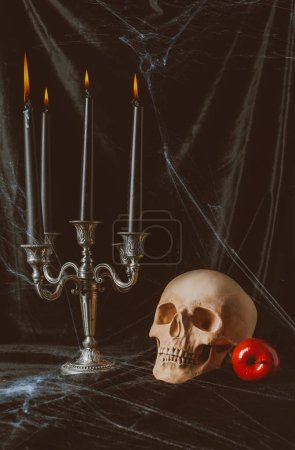 skull, red apple and candelabrum with candles on black cloth with spider web