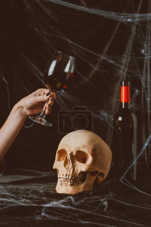 cropped view of woman holding glass of red wine near skull on black cloth with spider web