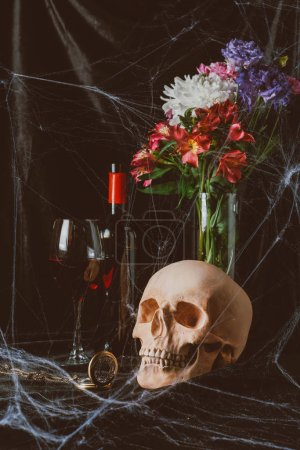 skull, red wine, vintage clock and flowers on black cloth with spider web