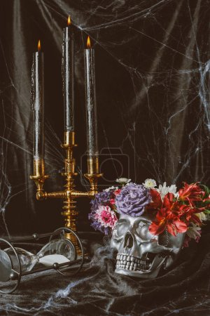 hourglass, silver skull with flowers and candelabrum with candles on black cloth with spider web, decorations for halloween