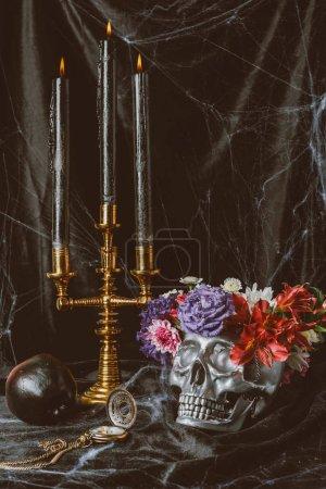 Silberner Totenkopf, Kerzen und Halloween-Dekorationen auf schwarzem Tuch mit Spinnennetz