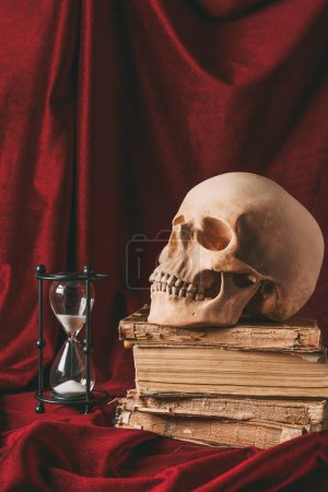 halloween skull on ancient books with hourglass on red cloth