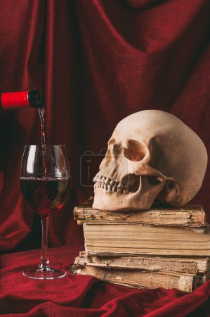 red wine, halloween skull on ancient books on red cloth