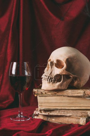 halloween skull on ancient books with wineglass on red cloth