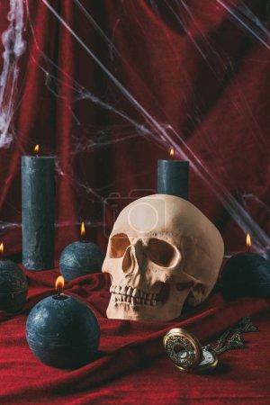 Foto de Cráneo, reloj vintage y velas negras en tela roja con tela de araña para halloween - Imagen libre de derechos