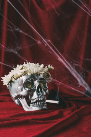 silver skull with flowers smoking cigarette on red cloth with spider web