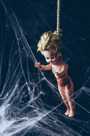 creepy dirty doll hanging noose in darkness with spider web