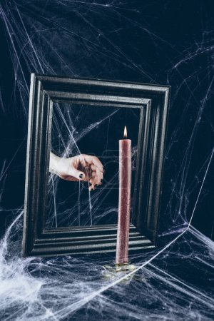 cropped view of mystic hand taking candle from mirror frame with scary spider web around
