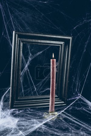 black frame and red candle in spider web, creepy halloween decor