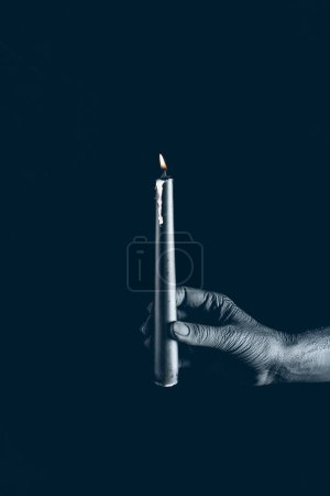 partial view of demon holding flaming candle in black hand, isolated on black