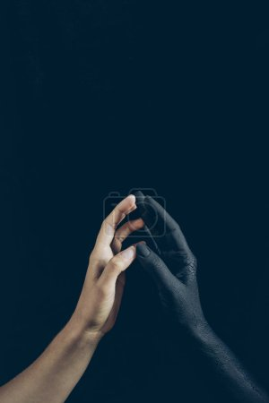 cropped view of woman touching with black demon hand isolated on black