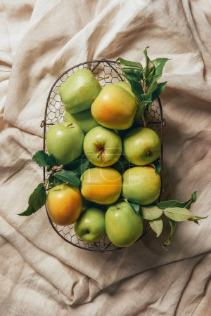 green apples in metal basket on sacking cloth