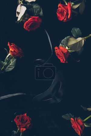 top view of black mask and beautiful red roses on black