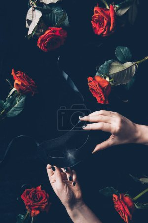 cropped shot of woman holding black mask and beautiful red roses on black