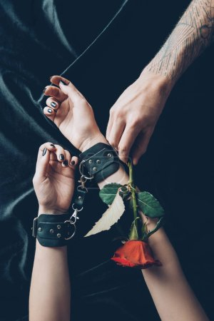 cropped shot of woman in black leather handcuffs and man holding red rose flower