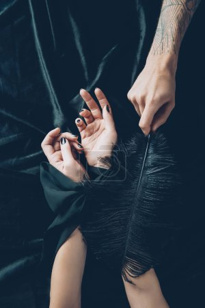 cropped shot of woman with tied hands and man holding black feather