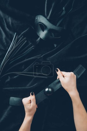 cropped shot of female hands with gag, leather whip and mask on black fabric