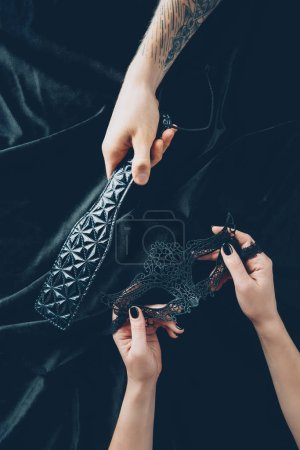 cropped shot of couple holding black lace mask and leather spanking paddle