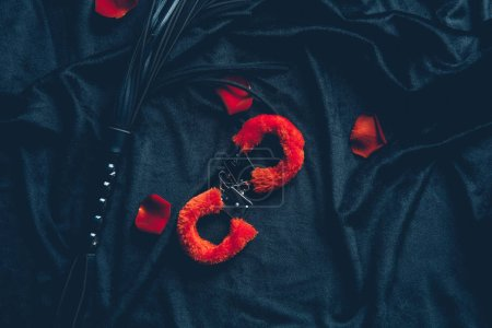 top view of red fluffy handcuffs, leather whip and rose petals on black fabric
