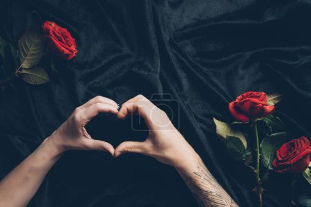 cropped shot of couple showing hand heart symbol above black fabric with red roses