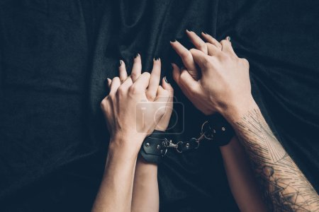 cropped shot of couple holding hands in foreplay, woman wearing leather handcuffs