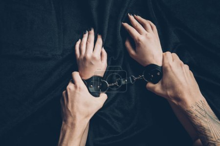 partial view of man holding hands of partner in leather handcuffs