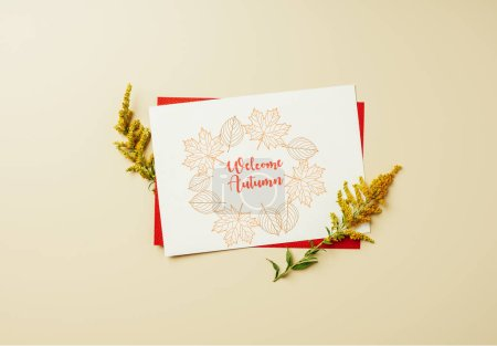 "flat lay with of wildflowers and white card with ""welcome autumn"" lettering on beige backdrop"