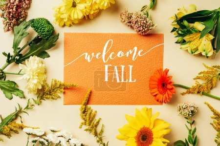 "flat lay with various wildflowers around orange card with ""welcome fall"" lettering on beige background"