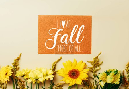 "flat lay with beautiful flowers and orange card with ""I love fall most of all"" inspiration arrangement on beige backdrop"