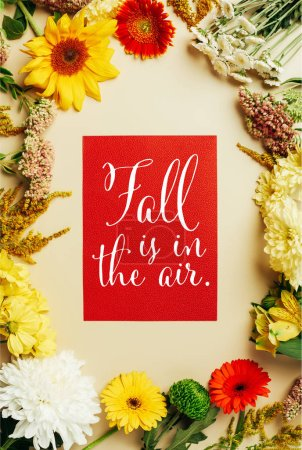 """flat lay with various beautiful flowers and red card with """"fall is in the air"""" inspiration on beige background"""