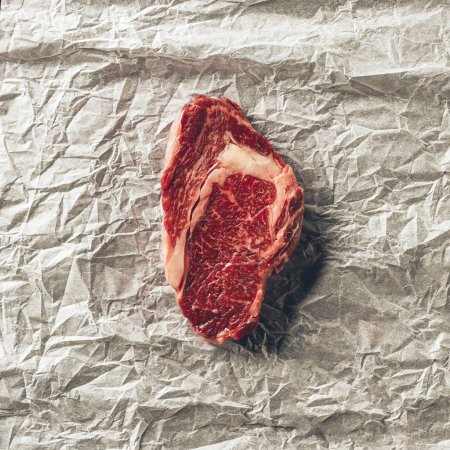 Photo for Top view of raw meat steak on baking paper in kitchen - Royalty Free Image
