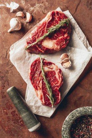 Photo pour Vue de dessus de deux steaks non cuits, pilon, mortier et épices sur la surface dans la cuisine - image libre de droit