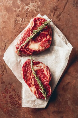 top view of two raw steaks with rosemary on baking paper in kitchen