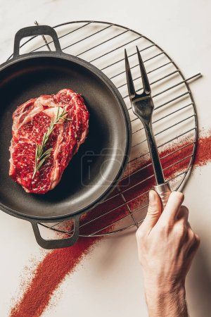 cropped image of man holding meat fork and cooking steak with rosemary in kitchen