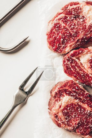 top view of three pieces of raw meat steaks with salt, meat fork and metal hook on white surface