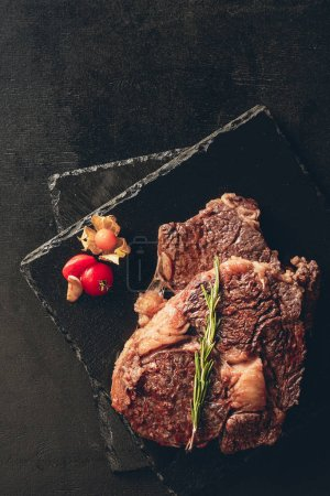 elevated view of roasted steaks with rosemary and berry on cutting boards in kitchen