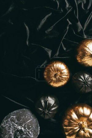 top view of traditional golden and black pumpkins on black cloth, halloween design
