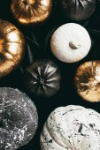 top view of traditional festive golden, black and white painted pumpkins for halloween party