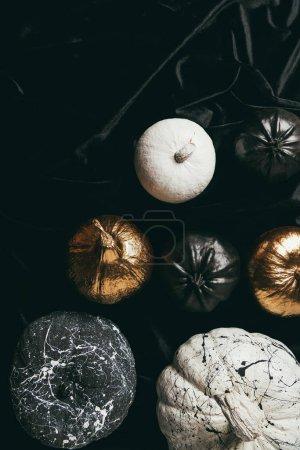 Blick von oben auf festlich dekorative goldene, schwarz-weiß bemalte Kürbisse auf schwarzem Tuch für die Halloween-Party