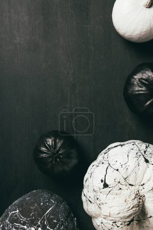 top view of black and white pumpkins with paint splatters on dark background with copy space