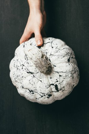 Photo pour Vue partielle de la personne qui détient la citrouille blanche avec une peinture noire splatters, décor d'halloween - image libre de droit
