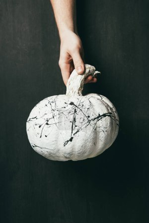 cropped view of person holding white pumpkin with black paint splatters in hand, halloween decoration