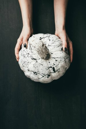 cropped view of woman holding white pumpkin with black paint splatters, halloween decor