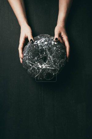 Photo pour Vue recadrée de femme tenant une citrouille noire avec éclaboussures de peinture en mains, décoration de halloween - image libre de droit
