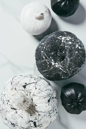 top view of decorative black and white pumpkins with paint splatters, halloween composition