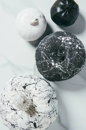 top view of decorative halloween black and white pumpkins with paint splatters