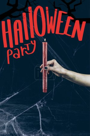 "cropped view of gothic woman holding red candle in darkness with spider web with ""halloween party"" lettering"
