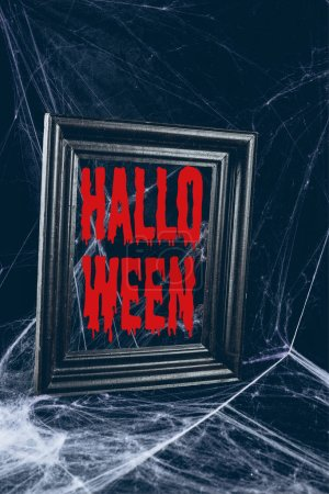 "black frame in spider web, creepy decor with ""halloween"" lettering"
